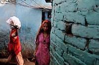A lady standing in an alley at Katputly colony in New Delhi, India. 14.11.2009. Kathputly colony is a slum area in West Delhi. This slum seems like any other slum areas of modern India with dysfunctional electricity, non existing sanitation and poverty. As a part of Delhi, this is also ailed with water crisis. Large families live their lives crammed together in a single room with all the odds which complement poverty. One thing which differentiates this slum with any other is the people living in the colony. Nearly everybody in this slum is a traditional performing artist; and they have been migrating to this area for last 50 years from different parts of the country for a better livelihood. They are magicians, acrobats, jugglers, puppeteers, dancers and musicians. These artistes perform in star rated hotels, marriage ceremonies of the richer section, functions, and festivities all around the country and the world. Most of the artisans I met here, have performed in Europe and America but such opportunities are rare to come by. They struggle to keep their art form alive. They say that they don't get any help or support from the government for their basic needs and for the well being of the Kathputly colony -  though they have uphold the prestige of the country internationally. Polluted air, dirty alleys smelling of urine, colourful dress and sound of music characterise Kathputly colony, which is the one of its kind in India. Arindam Mukherjee