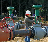 Construction worker checks installation of valves on new natural gas pipeline. Arkansas.