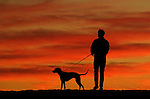 A man and his dog take in a vivid sunset perched atop a sand berm at Venice Beach near the end of a very warm first day of December in Southern California. Much of the rest of the country is experiencing winter storms.