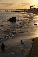 Sunset at Corona Del Mar State Beach, seen from a lookout above the beach at Inspiration Point.  I love how the wet beach sand looks golden / silver in color.  Three silhouetted figures stand in the foreground (a photographer, lighting assistant, and girl having quinceanera pictures taken of her in a fancy dress).