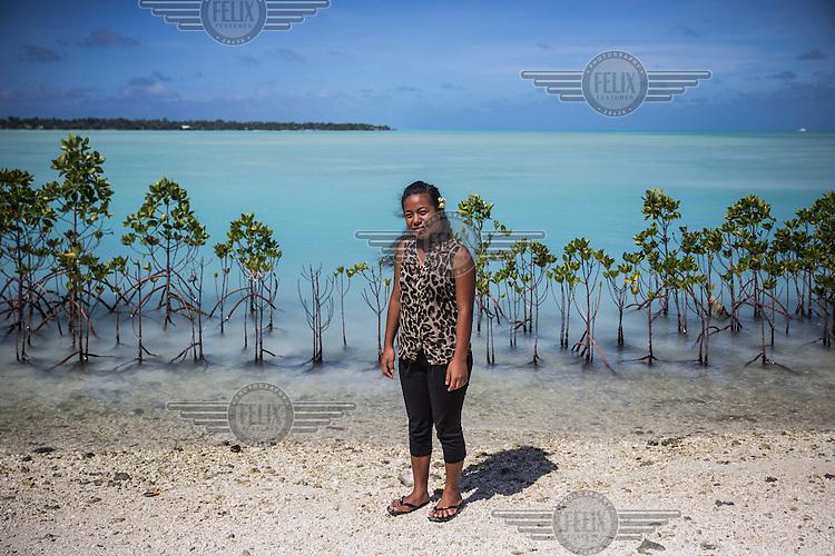 Tinaai Teaua, a member of Kiribati Climate Action Network (KiriCAN), standing in front of mangroves planted near Bonriki International Airport.