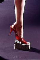 Woman's high heel shoe standing on stack of dollar bills