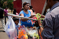 Razia Shabnam (in blue) buys some snacks as she picks her son, Saihaan, up from the St. Thomas School in Kidderpur after finishing her boxing training sessions in Calcutta, West Bengal, India. Razia Shabnam, 28, was one of the first women boxers in Kolkata. She was also the first woman in her community to go to college. She is now a coach and one of only three international female boxing referees in India.  Photo by Suzanne Lee for Panos London
