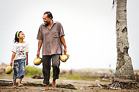 Father and Daughter, Burhananddin Yusut and  Ayu (9), make their way home with coconuts to celebrate the Feast of Ramadan. It will be the first meal in their newly built home, completed that afternoon. Their previous home was destroyed, and belongings lost in the Asian Tsunami a year earlier. <br /> <br /> Ayu, who told me she wanted to be a journalist, wrote in her diary; &quot;On Monday afternoon I was very excited because the house for me is completed. I also feel happy because we break our fasting together as a family and there are also overseas guests with us&quot; (translated). <br /> <br /> Banda Aceh, Indonesia