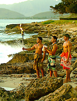 At Paradise Cove Luau, three Hawaiian kane (men) on the rocky shore at Ko Olina look out to sea at sunset. One holds a torch, another a conch shell - used for communication in early Hawaii. Image also available in horizontal format.