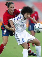 20 August 2004:  Julie Foudy battles for the ball against Japan forward Eriko Arakawa during the quarterfinals at Kaftanzoglio Stadium in Thessaloniki, Greece.     USA defeated Japan, 2-1 .   Credit: Michael Pimentel / ISI