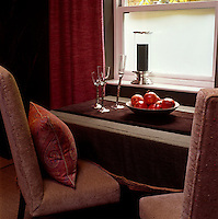 In the dining room two chairs are covered in a pinky-brown tweed with a paisley cushion next to a side table
