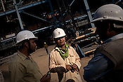 28 year old Chinese engineer, Zhu Haikuo from SEPCO is seen consulting and working with Indian engineers at the construction site of the Adani Power plant of 4620 MW capacity in Mundra port industrial city of Gujarat, India. Indian power companies have handed out dozens of major contracts to Chinese firms since 2008. Adani Power Ltd have built elaborate Chinatowns to accommodate Chinese workers, complete with Chinese chefs, ping pong tables and Chinese television. Chinese companies now supply equipment for about 25% of the 80,000 megawatts in new capacity.