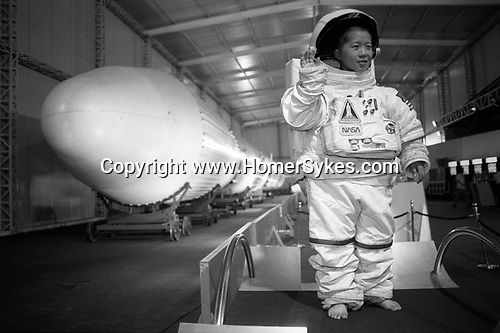 A small boy wearing an oversize NASA space suit while being photographed besides the Chinese &quot;Long March Number 3&quot; rocket, at the Zhongshan Park rocket exhibition. Shanghai, the Peoples Republic of China. 2000