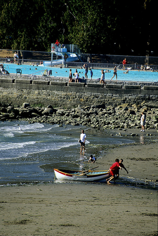 Lifeguards hauling lifeboat onto Second Beach in Stanley Park, with swimming pool in background, Vancouver, BC.