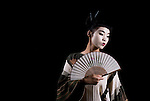 A young Japanese woman wearing a kimono and holding a fan