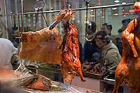 Roast duck hung in a restaurant window..Shanghai, February 2006.