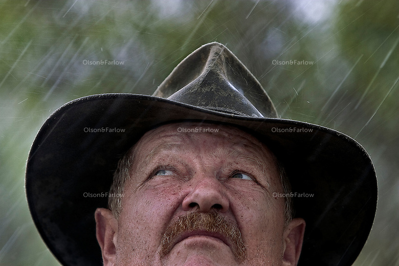 Portrait of Shady Lagoon cattle station manager John Gostilow as he raises looks up into the rain.  <br />