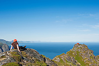 Hiker sits on mountain peak near Reinebringen, Moskenesoy, Lofoten islands, Norway