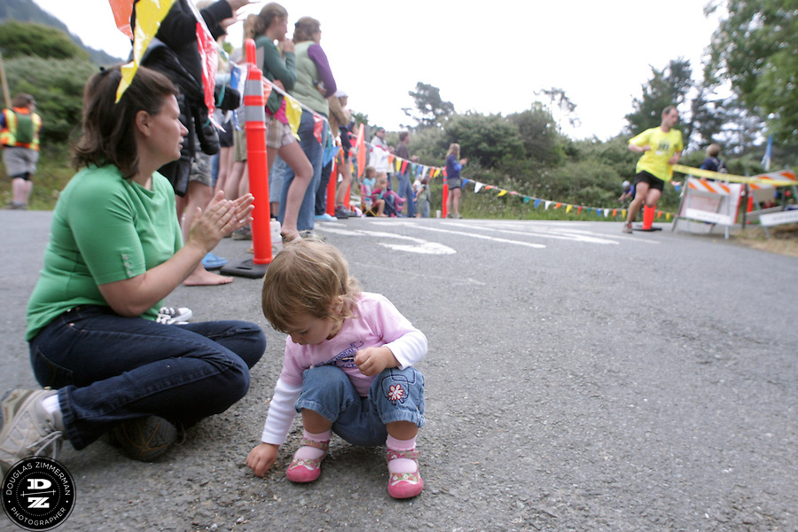 Jocelyn Leiserherndon (left w/green shirt) claps as a runner turns off of Highway 1 into the parking lot of Stinson Beach state park, while her daughter Gwendolyn, 2, is distracted during the 99th running of the Dipsea Race at Sintson Beach State Park in Stinson Beach, Calif. on Sunday June 14th, 2009.  They were both waiting for Brian Herndon (Jocelyn's husband and Gwendolyn's father) who was running the race.
