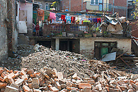 A young girl looking on surrounded by rubbish and construction materials in the Kathmandu Valley region in Nepal