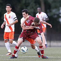 Boston College defender Nick Butler (4) attempts to control the ball as Syracuse University midfielder Stefanos Stamoulacatos (9) pressures.Boston College (maroon) defeated Syracuse University (white/orange), 3-2, at Newton Campus Field, on October 8, 2013.