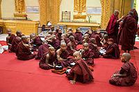 Myanmar, Burma.  Young Monks Waiting for Ceremony to Begin,  Alodaw Pauk Pagoda, Nampan Village, Inle Lake, Shan State.
