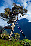 """The """"Swing At The End Of The World"""" is an adventure destination in Banos, Ecuador.  The swing carries the swinger out over a deep mountainous canyon and is attached to a treehouse called La Casa del Arbol.  The treehouse was constructed many years ago to monitor the Tungurahua Volcano, which can be seen in the background."""