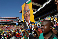 A man holds up a large portrait of Jacob Zuma at an African National Congress (ANC) election rally held at the Ellis Park Stadium in Johannesburg..