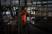 A factory worker monitors the oil extraction process at the Sipef oil mill in Sumatra, Indonesia.