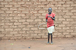 Monica Osman, 13, plays with a home made hula hoop in the Ajuong Thok Refugee Camp in South Sudan. The camp, in northern Unity State, hosts thousands of refugees from the Nuba Mountains, located across the nearby border with Sudan.
