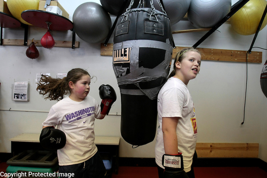 Rachael Carrell, 9, left, punches the bag as Shannon McRae, 11,  holds it still, during boxing class at Cappy's gym on April 29, 2008. Electives such a yoga, taekwon do, dance and boxing fill the gym requirement at Lake Washington Girls Middle School.
