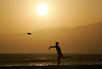 A man plays frisbee on Venice Beach on the first day of summer, or the Summer Solstice, June 21, 2010