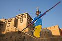 Rajasthani girl performing balancing act on high rope near entrance gate of Jaisalmer Fort, Jaisalmer, Rajasthan, India --- Model Released