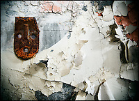 Broken and rusty hook on a wall covered in peeling paint, shot in an abandoned mental asylum.