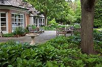 Backyard flagstone patio with hostas under shade trees