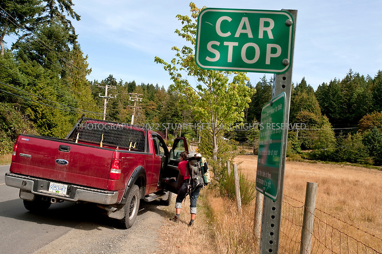 8/26/2009--Pender Island, British Columbia, Canada..Maren Lisac, 29, from Vancouver, Canada, hitches a  ride to the Pender Island ferry from a 'car stop', an official hitch hiking point on the island...©2009 Stuart Isett. All rights reserved.