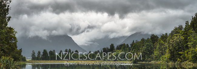 Moody weather over Lake Matheson with Fox Glacier Valley in background, Westland Tai Poutini National Park, UNESCO World Heritage Area, West Coast, New Zealand, NZ