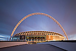 Wembley stadium in the warm glow of the setting sun. The home venue of the England national football team. Capacity 90.000 seats and including standing places 105.000. The Wembley arch which supports the roof is 134m high (440 ft).<br />