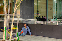 A labourer rests outside a luxury hotel.