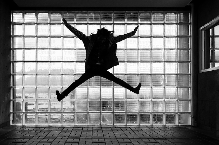 A sihouetted man jumping in from of glass brick, with reflections and movement.