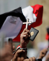 A man holding a cross and a quoran. Christians and Muslims came together on Friday prayers in Tahrir square, advocating peaceful co existence. Sectarian violence had flared in the wake of the revolution that saw president Hosni Mubarak removed from office.