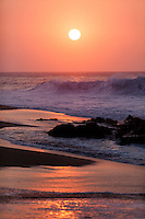 An orange sunset with breaking waves and rocks on the shore at Rock Piles beach on the North Shore, O'ahu