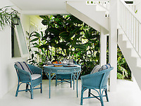 A Lloyd Loom occasional table and matching chairs is laid for breakfast on the swimming pool terrace