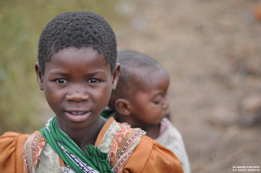 Girl in orange with baby - Basiyou Village - Chikwawa District - Malawi Africa
