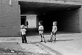 Young kids out playing, Wester Hailes, Scotland, 1979.  John Walmsley was Photographer in Residence at the Education Centre for three weeks in 1979.  The Education Centre was, at the time, Scotland's largest purpose built community High School open all day every day for all ages from primary to adults.  The town of Wester Hailes, a few miles to the south west of Edinburgh, was built in the early 1970s mostly of blocks of flats and high rises.