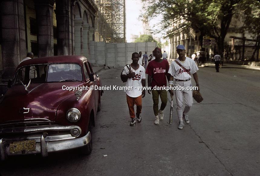 A 1956 Dodge parked on a Havana street as three men dressed in baseball unforms walk by in 1998.