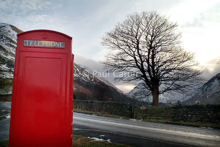 Bright red telephone box on the side of a road. The Lake District
