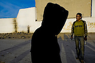 Young Moroccan immigrants stand in front of the wall in the port of Tanger, where names of those immigrants who reached to cross the European border controls are written, Morocco, 22 January 2007. Every day tens of Moroccan young men try to cross ilegally the Strait of Gibraltar. ?Harraga? (immigrants in Arabic) come to Tanger from all over Morocco. They try their good luck and hidden between the wheels of a truck they attempt to board on a ferry and get to Spain, eventually further to Europe. Considering the thorough checks at the port only few of them make it. Therefore they spend months living on a beach, in huts along the walls of the port, begging for food and waiting for the right night so as their dream about Europe came true.