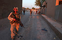 U.S. Army 4th Infantry Division, 1st Battallion, 12th regiment Sergeant Greg Pyrek from Denver, CO provides rear security as his squad moves down an alley during an evening foot patrol August 24, 3003 through Samarra, Iraq.