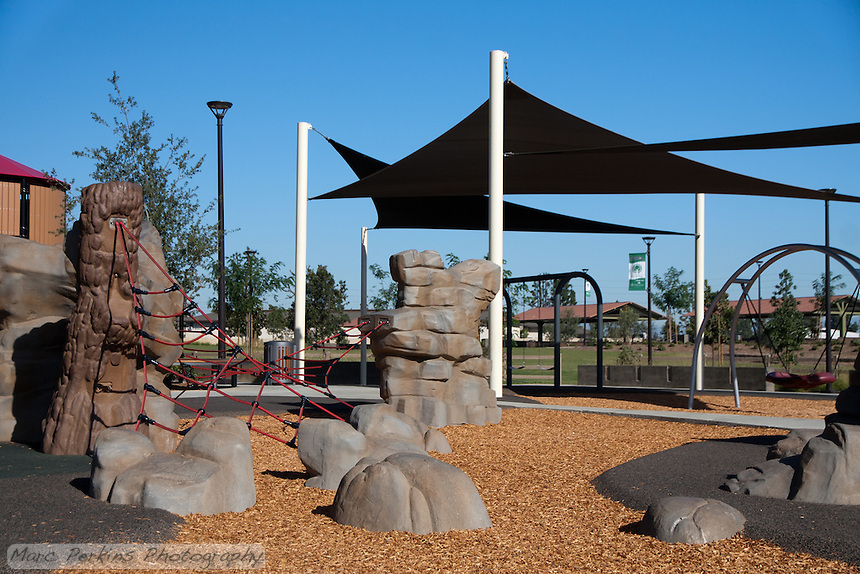 A broad view of one portion of the rope climbing area at Stanton Central Park. The ropes are suspended over either rubberized mats or wood chips.  A play structure with shade and the picnic pavilion can be seen in the background.
