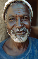 Mali. Province of Segou. Zambougou. An old man, wearing a hat, stands up near his home's door. © 2003 Didier Ruef