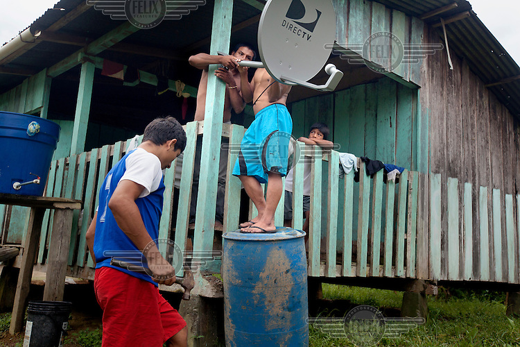 A group of young men install a satellite dish on a house in the Waorani community of Noneno that is located beside the Shiripuno River.