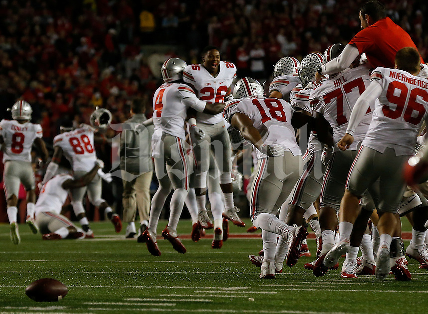 OSU football players celebrate while the ball sits on the field where the final play happened in overtime of their game at Randall Stadium in Madison, Wisconsin on October 15, 2016. OSU won 30-23. (Columbus Dispatch photo by Brooke LaValley)