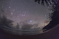 The southern hemisphere sky, from a beach near Port Douglas, Queensland, Australia. Jupiter is the bright object in the clouds at left, Sirius is above the people, and Canopus is above the bushes at right. Orion is rising left of centre, on its side. This is taken looking east from a latitude of 16.5&deg; South.